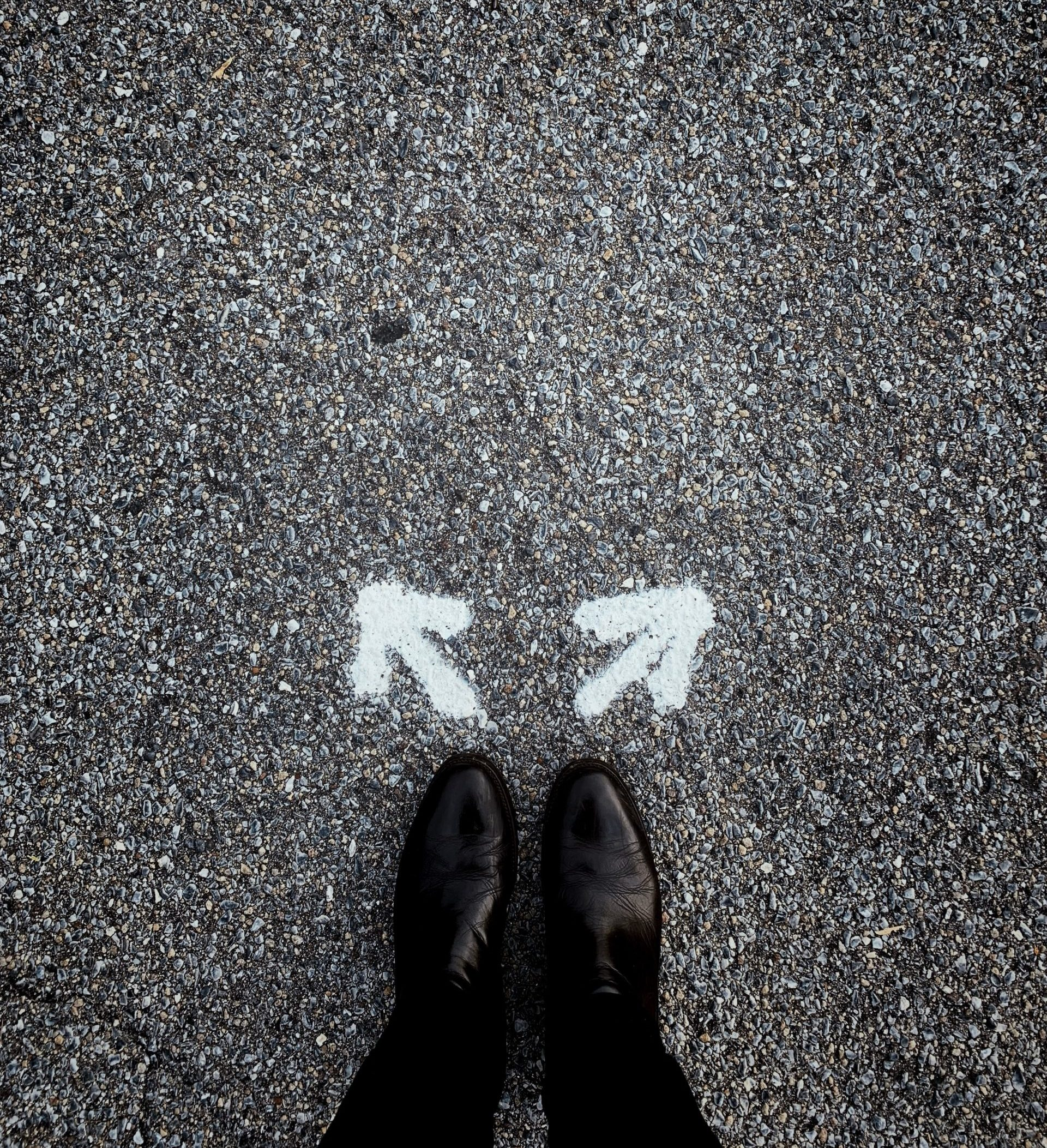 person's feet in front of a set up arrows pointing forward but in opposite directions